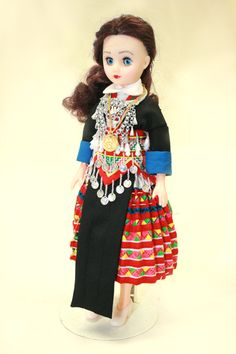 The style of clothing worn by this doll belongs to the Green (sometimes also called Blue) Hmong, a designation associated with the indigo or black batik skirts worn by the women in the group. Traditionally the skirts were much duller, with a little red appliqué work, but over the years they have become more vibrant by using a variety of the many colorful fabrics available. The jacket is similar to that worn by other groups of Hmong, hence the blue cuffs on the sleeves. A plain black apron…