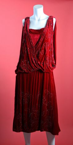 1920s Beaded Red Silk Velvet Dress. Lined with fabric that feels like silk. Sophisticated draped front, shoulder criss cross bands, and medallion style beading at the hips.