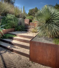 steps from upper level to lower through the retaining wall connecting gravel…