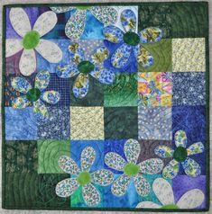 baby quilt with applique of flowers - great idea for a table top for summertime.....which I need