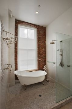 This shower-bath combo that literally has it all — an exposed brick wall, a claw-foot tub, and so much room for a refreshing shower.
