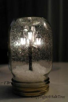 What a unique way to create a holiday glow! I was delighted to come across this unique winter craft created by SaltTree- simply made with a mason jar, miniature street light found at a dollar store (that really lights up!), glue, white glitter, and fake snow.  I think these would make special holiday night lights or look great on a Christmas mantle by Joann E Granger