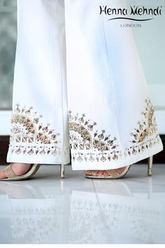White raw silk trousers with cut work and embellished with crystals and diamantes. Available in trousers or boot cut trousers. Can be ordered in black colour. New Embroidery Designs, Applique Designs, Pakistani Formal Dresses, Sewing Pants, Salwar Designs, Cut Work, African Lace, Indian Designer Wear, Sleeve Designs