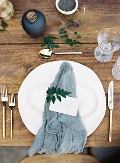 Table setting with muted blue tones and touches of gold with small bits of trailing foliage xx