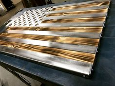 "Burnt 3 dimensional, Hand oiled pine, wrapped in a folded ""Polished US Flag"" / Metal Art Available in 2, 3 and 4 foot wide 2 Footers = 24""3 Footers = 36"" 4 Footers = 42"" Cut from 16 gauge, cold rolled, mild steel (very strong)Ground and polished, then covered in 3 layers of glossy clear coatFlag is set in grooves and"