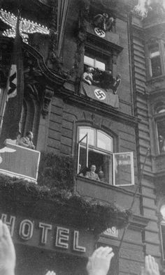 3.7.1936 - Köln, Germany: Hitler acknowledges the crowd's cheers from the balcony of the Dom Hotel after the reoccupation of the Demilitarized Zone of the Rhineland | Imperial War Museums