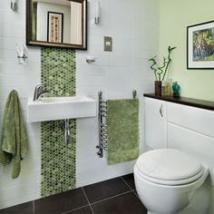This soothing green bathroom uses vertical stripes of mosaic tiles to make the ceiling seem higher. Built-in cupboards on either side of the toilet wth a counter-top above provides useful storage and display space.