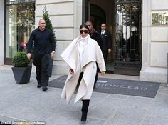 Arriving in style: As she landed at her Parisian hotel, Kim wrapped up in a large cream dr...