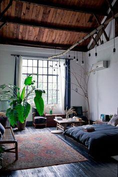 Bedroom: wooden beams, white walls, hanging lights, moroccan rug, dark wooden floor, navy linens, plants, rattan bench