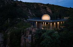 The chapel is built on rocky terrain and accessed via a route through the mountains.