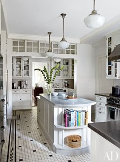Tracy Pollan and Michael J. Fox's New York City kitchen, features classic schoolhouse light fixtures, Shaker-style cabinetry, and stainless-steel and marble countertops.
