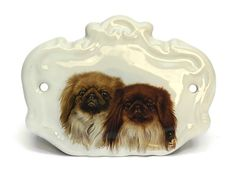 This delightful vintage French bedroom door sign dates to the early 1970s. The plaque has been created from glazed ceramic and has been decorated with a charming transferware illustration of a pair of pekingese dogs. The door sign has two small holes on either side for attaching to a
