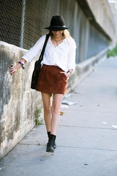 Style caster. Cowboy trend: brown leather mini skirt, white shirt, black ankle booties, hat, and bag