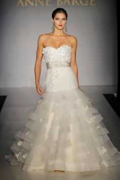 The Anne Barge Devereax shows off the body shape but does not forfeit the desire for a princess gown. The elongated bodice of the gown accentuates a slim torso, while the full ball gown skirt with thr