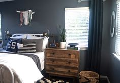 Steely blue wall color called Wall Street by Sherwin Williams. Dresser nightstand by West Elm. Teen Boys room.