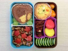 Bento Box gefüllt mit Gurke, Getrocknete Tomaten, Babybel, Tomaten, Quiche, Kuchen, Weintrauben, Champignons