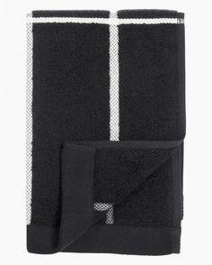 A guest towel made of thick cotton terrycloth featuring Armi Ratia's Tiiliskivi pattern. Material: cotton terry Colour: black, white Sizes: guest 30 x 50 cm x