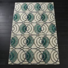 Shop Lucci Grey and Teal Rug. Ivory hand-tufted pile rug creates canvas for repeating rounds of grey and teal ombre. Viscose fibers bring sheen to the surface, adding even more dimension.