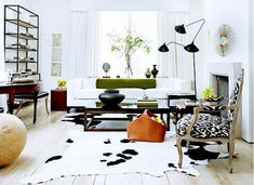 Living room with Serge Mouille lamp, ikat chair, and cowhide rug