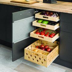 Des tiroirs en bois dans la cuisine accueillant des fruits et légumes et servant ainsi de garde-manger
