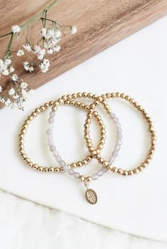 • Set of three beaded bracelets • Hamsa charm detail
