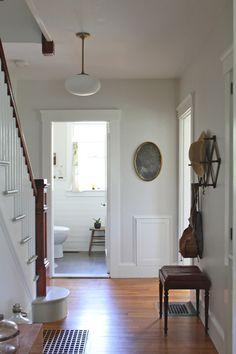 "Pale gray walls (""Classic Grey"" by Benjamin Moore), vintage pendant light, warm wood floor"