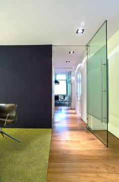 Glass door and wooden floor. Interior design by Casper Schwarz C4ID. Grey wall and lime green carpet.