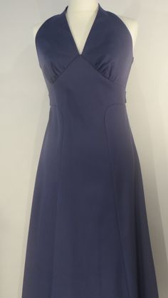 Vintage 1970s halterneck, 12.  Elegant 'French navy' halter-neck dress with a 'Marilyn' touch around the bust. Panelled and waisted with a belt that ties at the back. Flows from the hips. Great for packing into a suitcase for a touch of understated class as it doesn't crumple.   Size: 12 Measurements: B: 36, W: 30, H: 38, L: 51 Label: Unknown Decade: 1970 Material: Polyester Cleaning instructions: Machine wash at 30 degrees on a silk wash