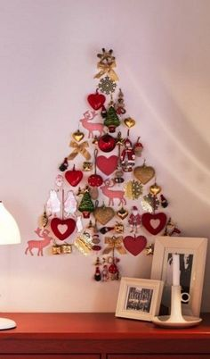 a Christmas tree shaped of christmas ornaments right on the wall