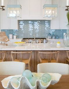 Glossy blue tiles for kitchen backsplash to mimic ocean waters. Home tour featured on Completely Coastal: http://www.completely-coastal.com/2016/08/pastel-blue-yellow-seafoam-home-decor.html