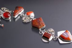 """""""Painting with Stones"""" series by Claudia Walsh    The bracelet is fused, forged and fabricated in sterling silver, 14k and 18k gold. The stones in the toggle bar are carnelian. The link stones include carnelian, handcut Mary Ellen jasper, ox blood coral, moonstone, handcut red moss agate, handcut red tiger's eye and handcut red lace agate."""