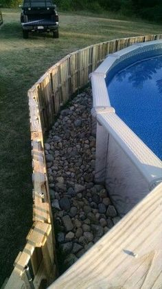 Pallet fence-  above ground pool camouflage.  Stone border between.