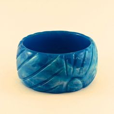 Moulded to resemble the deeply carved look of bakelite, this glossy bangle bracelet is a deep rich blue - the color of blue raspberry candy! A radiating sun pattern creates the ridges and smooth curves on either side. White swirls form fabulously marbled clouds and streaks within.