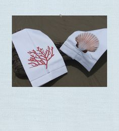 Coral towel. Scallop Shell towel. Seaside chic. French knot coral embroidery and embroidered scallop shell design creates a beach chic accent for the bath or kitchen. White cotton creates a clean, crisp look and feel and hemstitch detailing gives it that little something extra.