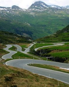 San Bernardino Pass - Switzerland. The road connects the towns of Misox and Hinterrhein. The pass is located at 2,065 meters and the road has incredibly smooth roads, a lot of hairpins and challenging bends and of course, amazing scenic views. The road also goes through an impressive 6.6 km long tunnel.