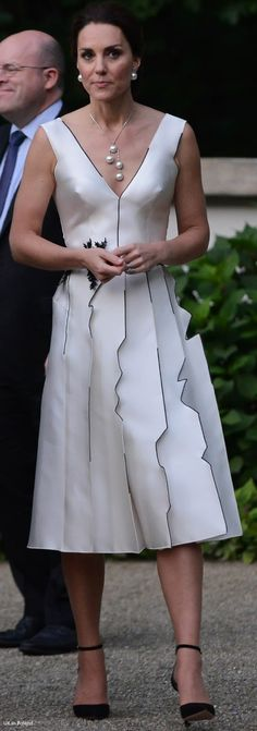 Kate's dress is by Polish designer Gosia Baczynska. The Duchess tends to wear at least one piece by a local designer when touring another country and tonight's reception seemed the perfect time to choose a Polish design. The dress is really quite a departure from Kate's signature; it's a contemporary piece but also quite edgy for the Duchess. The black and white dress features a plunging neckline and leaf embellishment at the waist.