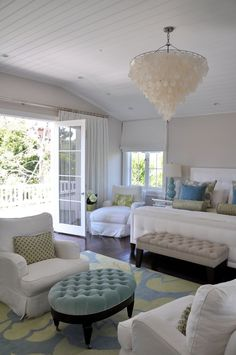 Glam Beachy Bedroom with Tufted Ottoman & Capiz Chandelier - wall color is F Skimming Stone - by Brooke Giannetti in Coastal Living