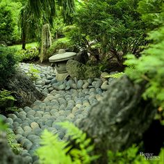 """Japanese gardens usually utilize representation. Here, tumbled gray river rocks of uniform size have been carefully arranged in this meandering dry streambed to create the illusion of flowing water. Ferns and evergreens line the stream, softening its """"shoreline."""""""