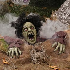 """Clawing Zombie Groundbreaker With LED Eyes. Make your Halloween decorations come to life with this zombie that appears to be breaking through the ground to join the fun. This zombie laughs as its eyes flash red. Latex and fabric. Requires 2 """"AA"""" batteries, not included. 10"""" x 25"""""""