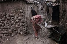 Feb. 4, 2013. An Afghan refugee girl holds on to her headscarf against the wind while making her way along a muddy alley of a slum on the outskirts of Islamabad, Pakistan.