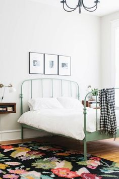 Feminine yet minimal bedroom with a floral area rug, a white sconce, and a green…