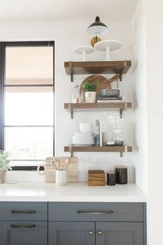 Modern kitchen with deep walnut open shelves, white countertops, and dark blue cabinets in Benjamin Moore's Cheating Heart