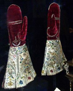Pair of mittens, c. 1600 - Embroidered in England, said to have been a gift from Elizabeth I to her maid of honor, Margaret Edgcumbe (1560-1648). Crimson velvet, white satin, embroidered with silver gilt thread, colored silks, beads, and spangles. IMAGE: Elizabethan gloves at the V&A Museum.