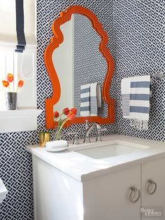 To keep shades of orange fresh and modern, pair with cooler colors like dark charcoal or deep blue. In this powder room, navy blue wallpaper in a graphic print provides a contemporary backdrop for an elegant orange mirror, while white trim and a neutral vanity provide contrast./