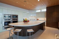 Sleek modern kitchen in the California desert has dark wood cabinetry and curved central island, wood panel ceiling tile, white cabinetry and countertops and stainless steel appliances.