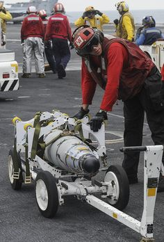 GULF OF OMAN (June 13, 2013) – Aviation Ordnanceman Airman Michael Zdunowski prepares to move a bomb across the flight deck of the aircraft carrier USS Nimitz (CVN 68). Nimitz Strike Group is deployed to the U.S. 5th Fleet area of responsibility conducting maritime security operations and theater security cooperation efforts. (U.S. Navy photo by Mass Communication Specialist 2nd Class Devin Wray/Released)