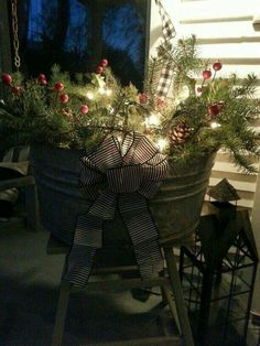 Easy Christmas porch decor idea: fill any metal or wood bucket or wicker basket with gathered twigs, branches, evergreens, ornaments,etc. then pile on a strand of Christmas lights! Christmas Porch, Primitive Christmas, Outdoor Christmas Decorations, Rustic Christmas, Christmas Fun, Christmas Wreaths, Christmas Planters, Christmas Lights, Christmas Inspiration