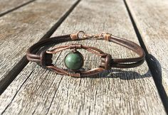 This genuine leather bracelet surrounds a copper wire focal piece with an Indian agate bead in the centre. It currently measures 7 3/4 inches but can be adjusted. This copper bracelet would make a gorgeous and unique gift.  The centre piece has been oxidised to give it an antique look and has then been given a coat of renaissance wax to protect and seal from further oxidisation. Copper will still oxidise over time, but that is part of its natural beauty.  If your copper items start to lo...