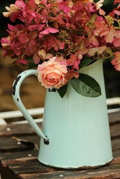 Peach and wine colored flowers displayed in light green pitcher