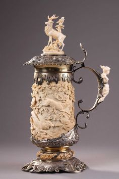 - A SILVER MOUNTED RELIEF CARVED IVORY TANKARD.<br/>  19 TH GERMAN WORK.